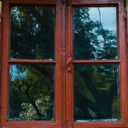 Wooden window frame painted brown. Traditional rustic window. Glass reflecting  green trees. Rustic panel of vintage