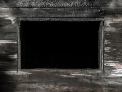 Wooden window of house after the fire. Coals on the logs. The ashes of the house from fire. Burnt destroyed cottage. black wooden frame.