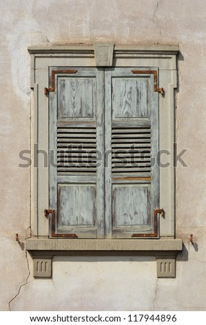 Wooden window shutters - Closed old shuttered weathered wooden window in the Alsace, France