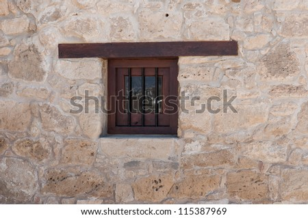 wooden window with a lattice in the stone wall