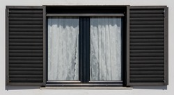Wooden window with black shutters on a white facade