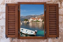 Wooden window with open shutters against the background of the stone wall of the house. Looking in the window, you can see the enchanting seascape and close-ups of the moored motor boat