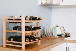 Wooden wine supply with bottles on table in modern kitchen.