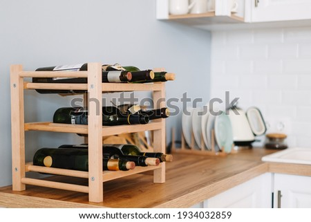 Wooden wine supply with bottles on table in modern kitchen. Zdjęcia stock ©