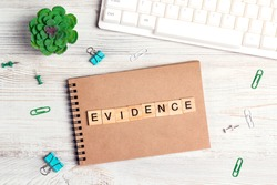 Wooden word Evidence in workspace on paper notepad with computer keyboard, supplies  and green plant on light wood background. Top view, flat lay office desk table.
