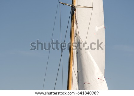 Wooden yacht mast with sails.