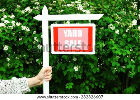 Wooden Yard Sale sign in female hand over green bush and flowers background