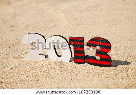 Wooden 2013 year number on the sand at a beach