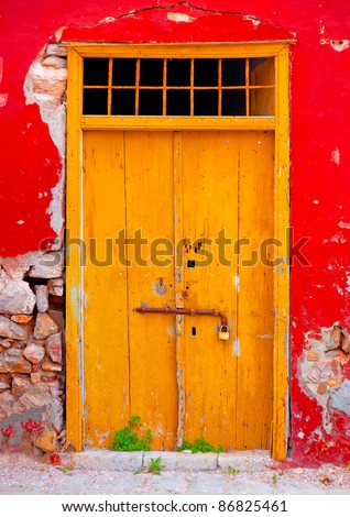 Wooden yellow beautiful door in an old red colored building in the small port Kamini of Hydra island in Saronikos gulf in Greece