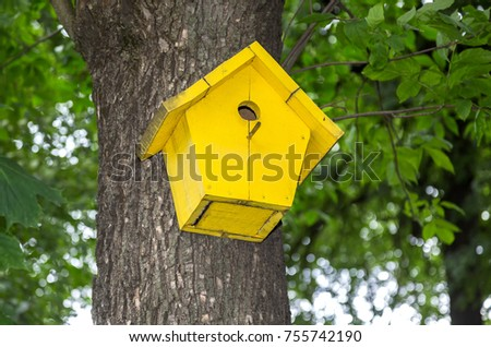 Wooden yellow birdhouse on a high tree in the public park #755742190
