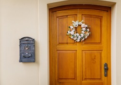 Wooden yellow door with a decorative flower wreath and a mailbox on a white wall
