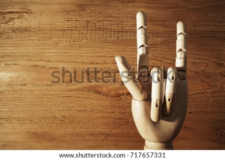 Wooden yellow hand raised with two fingers up, rock sign. on the background textured wall. Gesture, goat, horns, protection from evil. Index finger and little finger #717657331