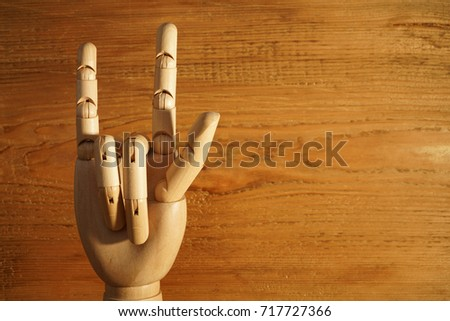 Wooden yellow hand raised with two fingers up, rock sign. on the background textured wall. Gesture, goat, horns, protection from evil. Index finger and little finger #717727366