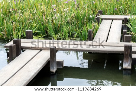 wooden zigzag bridge over a pond surrounded by irises in a Japanese garden on a summer day #1119684269