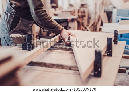 Woodwork and furniture making concept. Carpenter in the workshop marks out and assembles parts of the furniture cabinet close up