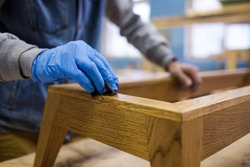 Woodwork oil being applied on wooden furniture. Close up view.
