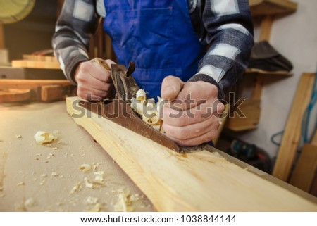 woodworker keeps in the hands of the plane,  removes chips from the wood and aligns timber