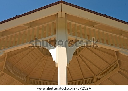 Woodworking detail of the roof structure of a gazebo against a blue sky in a park.