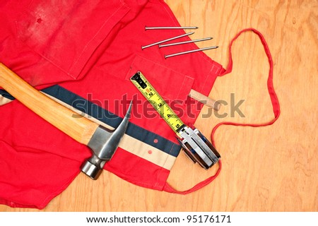 Woodworking tools including a hammer, tape measure, carpenter pencil and old red apron on a piece of plywood plank