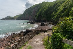Woody Bay near Martinhoe, Lynton and Lynmouth in Exmoor National Park, North Devon Coast, UK . View of entrance  with old harbour wall and rocky beach with heavily wooded cliffs and Crock Point.