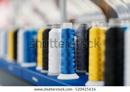 Shutterstock Wool and thread spools on desk used in textile industry