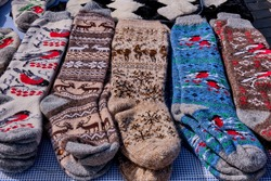 Wool handmade souvenirs of the mountain Crimea for tourists. Colorful warm wool knitted socks with patterns.