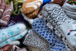 Wool mittens and socks. Ornament on socks and mittens. Mittens on the market counter. warm mittens, socks, woolen products.