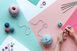 Wool yarn, cotton balls and knitting needles. Hands with crochet. Creative hobby craft. Paper background in pink, mint green, white. Pastel color hobby arrangement on layered paper background.