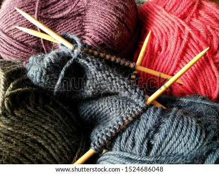 Wool yarn in different colors with wooden double point needles. The needles are being used for knitting socks, mittens or other projects joined in the round.