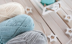Wool yarn milky, gray, mint color lie on a light wooden table/ Composition of wool balls and interior items: candle holder, garland, wooden box. Home comfort, knitting