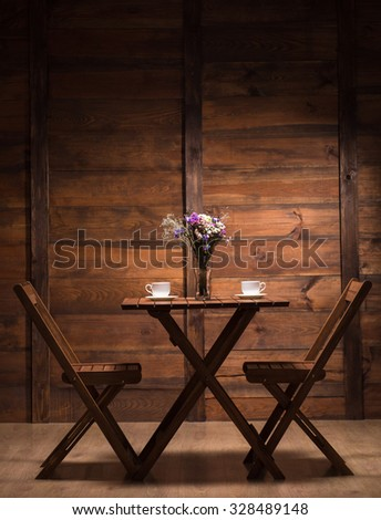 Woooden table and two chairs represented in cafe or restaurant for spending evening with a cup of coffee or tea.
