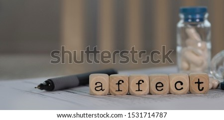 Word AFFECT composed of wooden dices. Pills, documents and a pen in the background. Closeup
