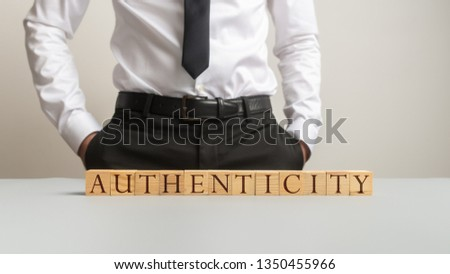 Word Authenticity spelled on desk with wooden cubes with businessman standing in background. #1350455966
