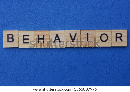 word behavior made from brown wooden letters lies on a blue table