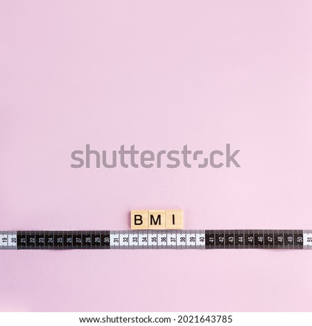 Word BMI on wooden blocks and measuring tape on pink background. Control concept body mass index. Copy space. Square orientation.