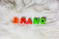 Word Brand spelling by colorful wooden abc letters at fluffly, faux fur white background, fashion, social media industries, style concept