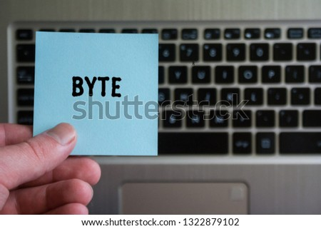 word BYTE on sticky note hold in hand on laptop keyboard background.