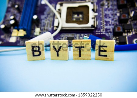 Word BYTE on the wooden blocks with computers mainboard background. Information technology background with mainboard.