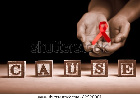 Word 'Cause' from wooden block with hand holding red ribbon on dark background