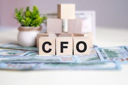 Word CFO is written on wooden cubes arranged in a pyramid. The cubes are located on the banknotes lying on the table. In the background a green plant in a pot. CFO - short for Chief Financial Officer.