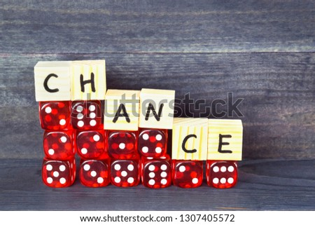 Word Chance written on wooden cubes and red dice on the dark background.  #1307405572
