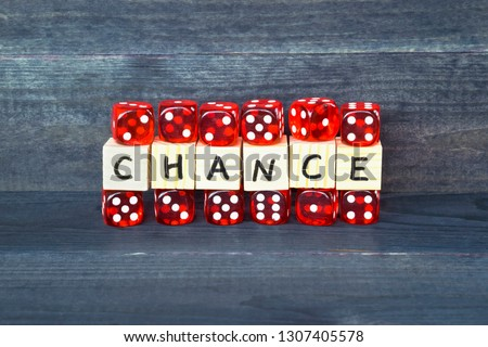Word Chance written on wooden cubes and red dice on the dark background.  #1307405578
