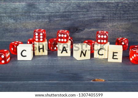 Word Chance written on wooden cubes and red dice on the dark background.  #1307405599