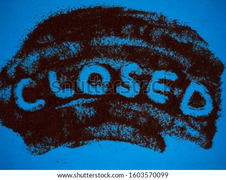 Word Closed hand written on roast ground coffee on a blue background top view. Can be used as creative Closed sign for coffee shops, cafes and bars.