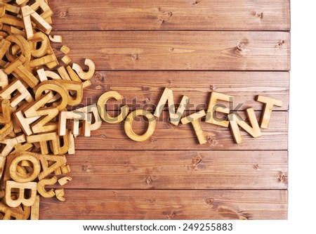 Word content made with block wooden letters next to a pile of other letters over the wooden board surface composition