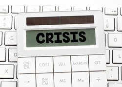Word crisis on the screen of the calculator located on a computer keyboard. Concept in business. Global economic crisis related to coronavirus.