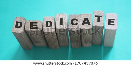 Word Dedicate on a row of wooden blocks. Devotion dedication love concept. Stockfoto ©