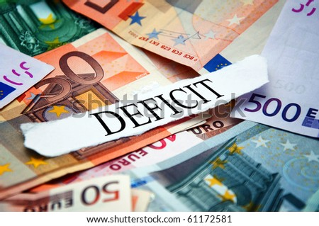 """Word """"Deficit"""" printed on a piece of paper and placed above the pile of euro banknotes"""