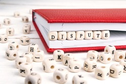 Word Dispute written in wooden blocks in red notebook on white wooden table. Wooden abc.