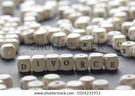 Word - Divorce made up of wooden letters on the table with wedding rings. #1024231951